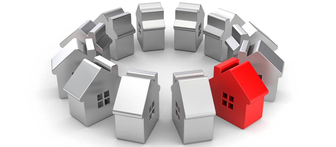 Steel figures of houses one of which red. 3d illustration